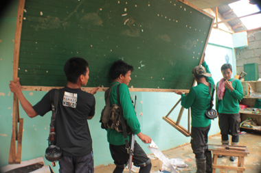 HANDYMEN. Communist guerillas help fix one of the primary schools damaged by typhoon Pablo in Compostela Valley Province. (davaotoday.com photo by Ace R. Morandante)