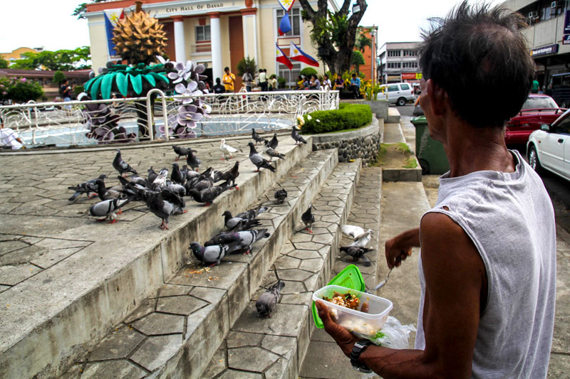 SHARING IS LOVING.  A shoe repair man shares his modest lunch with the doves outside the Davao City Hall building.  (davaotoday.com photo by Ace R. Morandante)