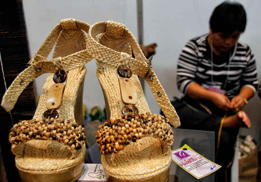 BUTUAN CRAFT  Maylene Cutor of Ivory.07 Arts and Craft from Butuan City, demonstrates how to weave dried water lily into a pair of sandals which they are displaying now in the Mindanao Trade Expo 2013 at Abreeza Ayala Mall until August 25. Cutor said they can produce a maximum of seven pairs of sandals a day. (davaotoday.com photo by Medel V. Hernani)
