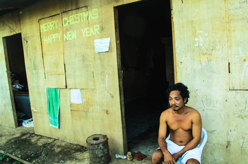 With a Christmas greeting on the wall, this resident longs for a permanent house outside of this bunkhouse built by DSWD in Baganga, Davao Oriental for Typhoon Pablo survivors. (davaotoday.com photo by Ace R. Morandante)